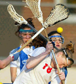girl getting hit in the head with yellow lacrosse ball with 2 girls standing in the background standard equipment yellow lacrosse ball