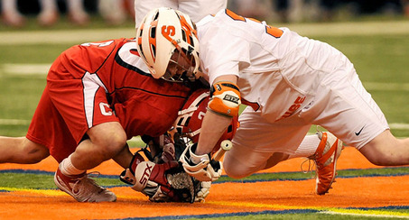 2 players facing off one in a red uniform the other in a white uniform standard equipment is regulated lacrosse ball lacrosse stick and regulated protective gear