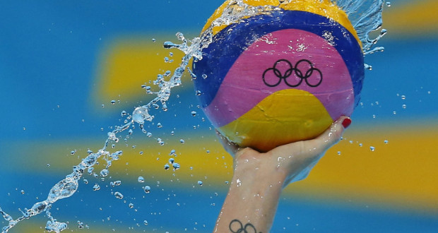olympic water polo ball in the air with water flung around it polo player with olympic tattoo on wrist official olympic water polo ball