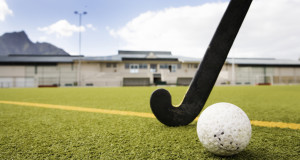field hockey ball on a turf field with a field hockey stick behind standard equipment field hickey ball is solid color