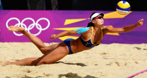 olympic beach volleyball player diving for yellow volley ball