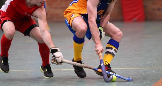 2 players going for the same ball indoor field hockey standard field hockey equipment field hockey stick and field hockey ball