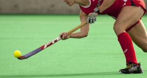 olympic field hockey yellow ball being handled by a women wearing a red uniform basic standard equipment for field hockey field hockey ball and field hockey stick