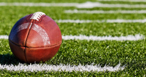 american football laying on a field with the laces pointing up official high school standard equipment football ball