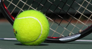 tennis ball on the ground of a tennis court with a tennis racquet behind it basic equipment for tennis