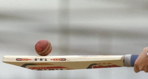 A cricket ball is resting on top of a cricket bat these are the regulated cricket ball and bat