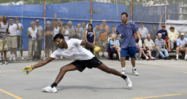 man reaching to hit the handball ball while onlookers stand in the background official equipment handball ball