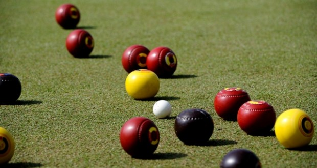 lawn bowls mid play red balls yellow ball black balls white ball basic equipment for lawn bowl different colored balls per player
