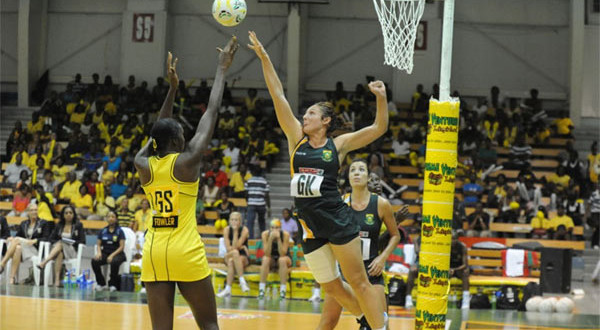 girl in green blocking shot by girl in yellow netball basic equipment ball and net hanging of a pole