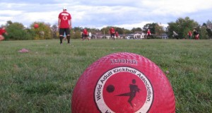 WAKA regulated kickball ball in foreground with a kickball game going on in the background basic equipment for kickball regulated WAKA kickball ball