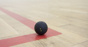 black squash ball on the corner of the squash court basic equipment for squash small black squash ball