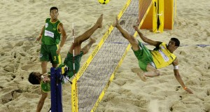 2 guys playing after ball over volleyball net with feet footvolley basic equipment ball and beach volleyball net