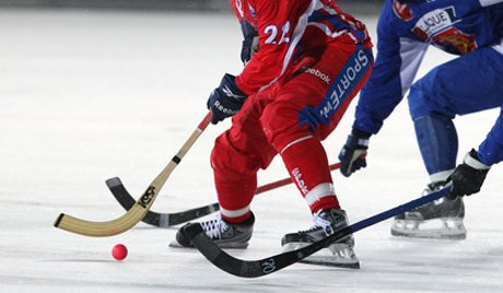 2 bandy ball players one red one blue following orange ball 3 hockey sticks basic equipment hockey sticks orange round bandy ball