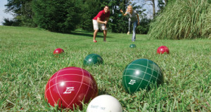 2 people playing bocce ball in a grassed area 2 green balls 3 red balls one white ball basic equipment bocce ball bocce ball set with different colored balls
