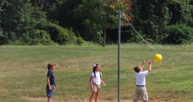 school kids playing tetherball yellow ball equipment on string on a pole with 2 kids playing and one kid watching