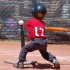 little kid swinging a bat at the tee ball ball on the tee ball stand red shirt helmet basic equipment for tee ball