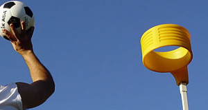 man shooting ball into korfball net yellow ring on top a pole basic equipment for korfball