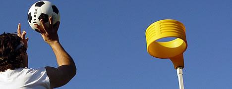 man shooting ball into korfball net yellow ring on top a pole basic equipment for korfball