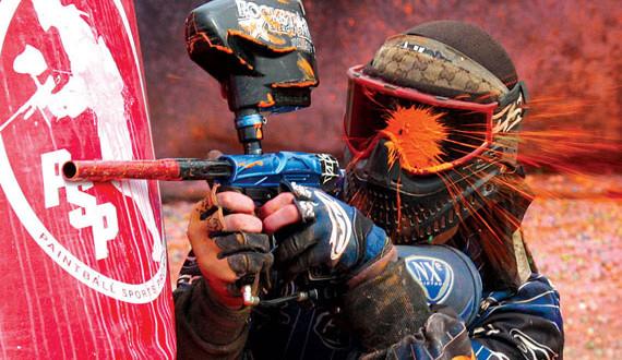 paintballer hiding behind barrier shot in the eye mask by orange paintball basic equipment paintball body gear paintball gun and paintball balls/bullets