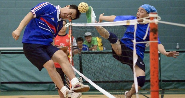 sepak takraw game one opponent is head budding the ball while the other is kicking the ball over a net that is similar to a volleyball net standard equipment for sepak takraw