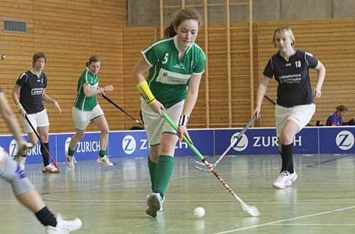 girl in green uniform running up floorball court with a player in black following standard equipment for floorball