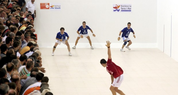 traditional valencian pilota game with 3 men in blue while a man in red is about to sweep down to hit the ball standard equipment for valencian pilota game