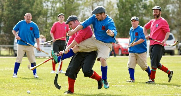 Shinty game with 3 men on blue team and 3 men on red team regulated equipment for shinty