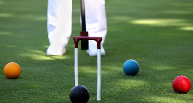 person in white pants standing behind a croquet game with orange/yellow ball black ball blue ball and red ball standard equipment for croquet