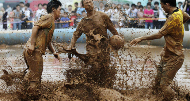 Image: Players compete in the 2012 Swamp Soccer World Cup China match